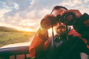 Man with binoculars at sunset